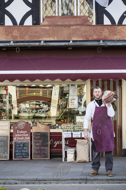 Man wearing apron standing on pavement outside butcher shop, carrying large piece of beef on his shoulder
