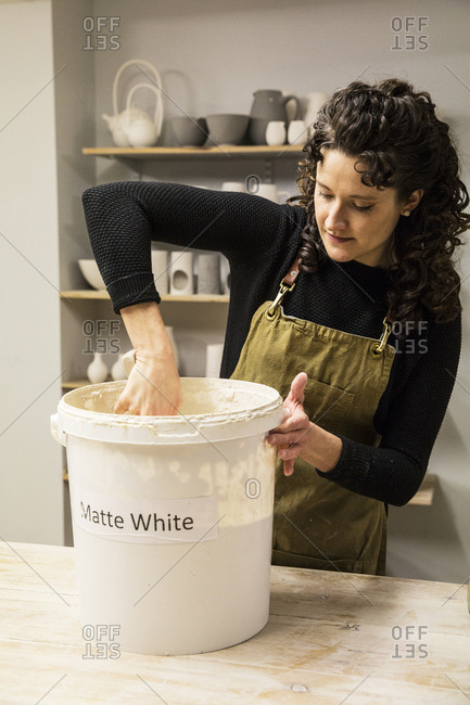 Woman with curly brown hair wearing apron standing in pottery workshop, dipping vase into pail with white glaze
