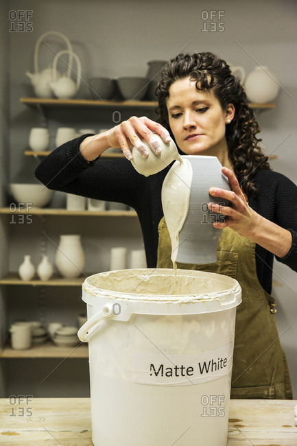 Woman with curly brown hair wearing apron standing in pottery workshop, pouring white glaze over unfired vase