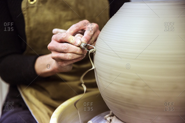 Close up of potter wearing apron working on spherical clay vase on pottery wheel
