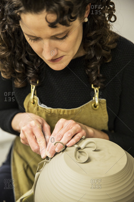 Close up of woman with curly brown hair wearing apron working on spherical clay vase on pottery wheel