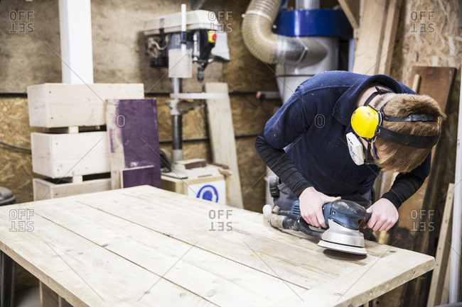 Man wearing ear protectors, protective goggles and dust mask standing in a warehouse, using sander to smoothen piece of wood