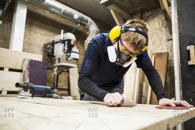 Man wearing ear protectors, protective goggles and dust mask standing in a warehouse, working on a piece of wood