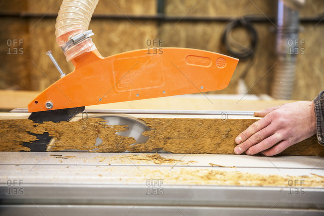 Close up of person cutting piece of recycled wood with a circular saw