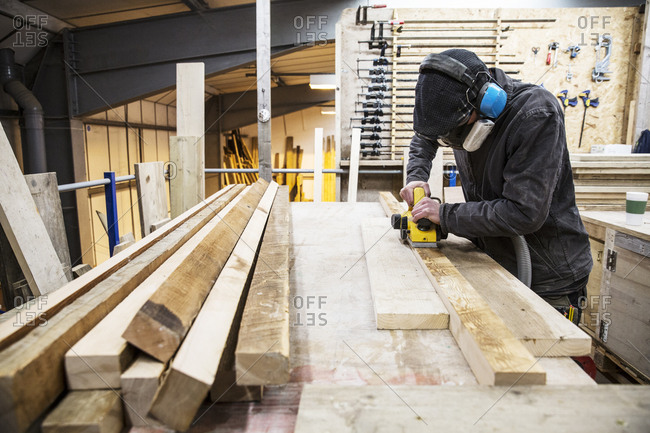 Man wearing ear protectors, protective goggles and dust mask standing in a warehouse, sanding planks of recycled wood