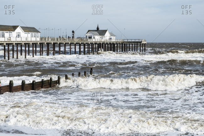 Seascape with waves rolling onto beach near groyne and white wooden buildings on a pier