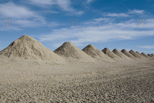 Mining tailings creating row of dirt piles in a desert, extraction