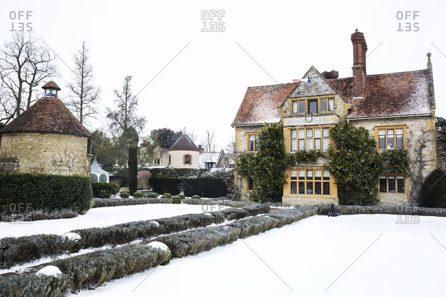 Historic 17th century manor house with tall chimneys, a hotel with snow covered grounds in winter