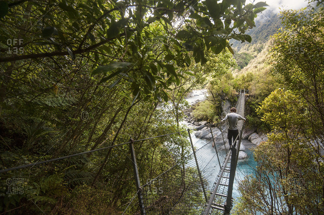 Man walking across a swing bridge over a beautiful blue river