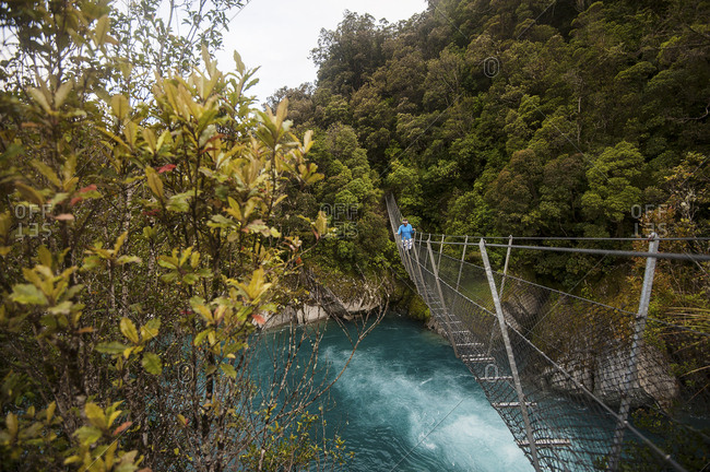 Man crossing a swing bridge over a beautiful blue river