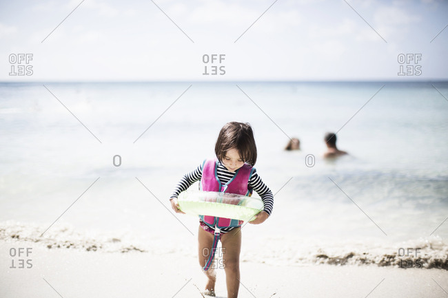 Toddler girl coming out of water with buoy