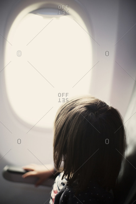 Young girl on plane looking out window