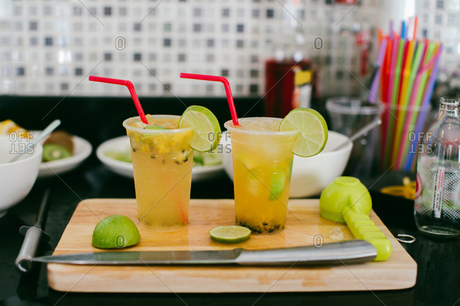 Two passion fruit cocktails with lime on cutting board with knife and citrus squeezer