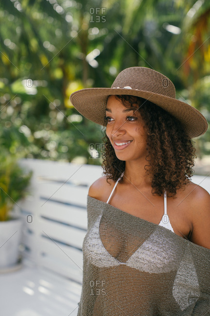 Portrait of a smiling young woman with curly hair wearing a bikini, sheer swimsuit cover-up, and hat