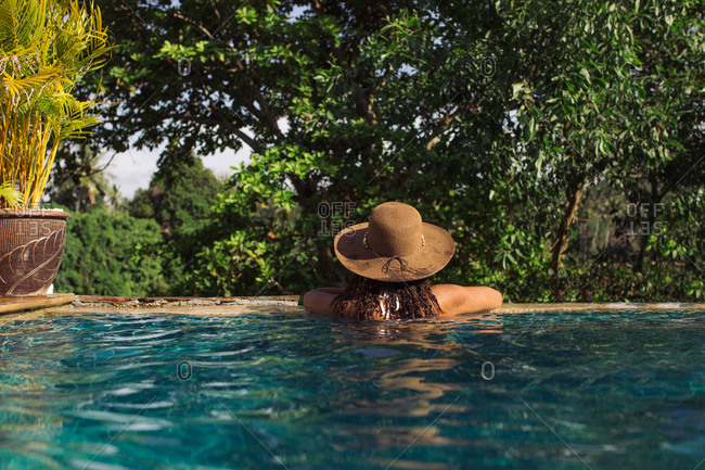 Back of woman wearing hat resting at edge of swimming pool
