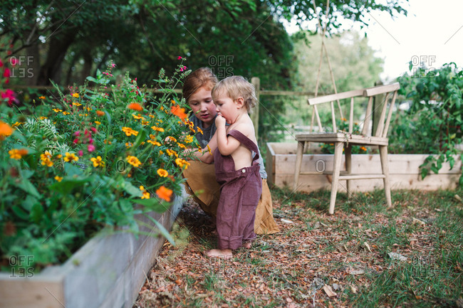 Toddler and bigger sister picking flowers in backyard