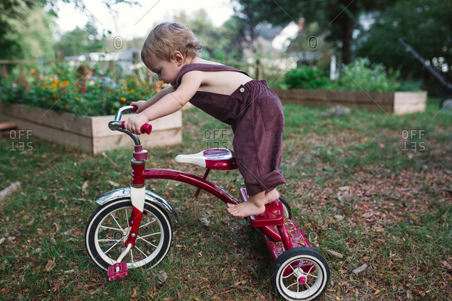 Young child balancing on trike in grass