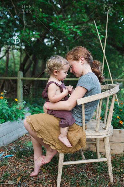 Siblings sitting in outdoor chair by flowerbed