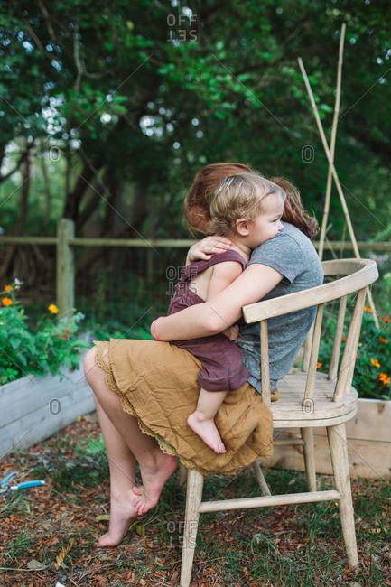 Toddler leaning on older sister's shoulders in garden