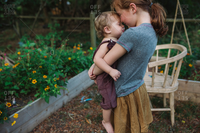 Sweet siblings standing in rural backyard together