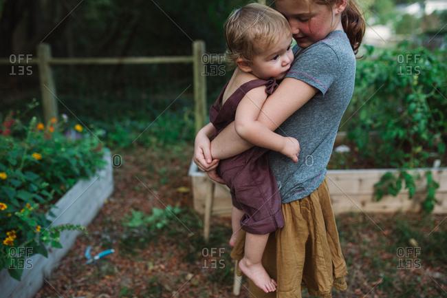 Big sister tenderly holding baby sibling in backyard