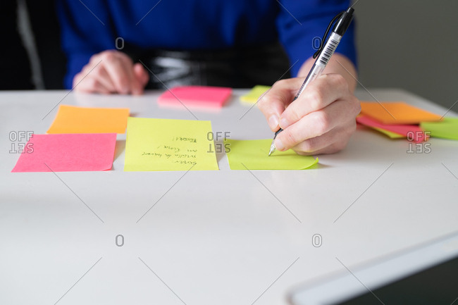 Close up of woman's hand writing notes on sticky notes laid out on table