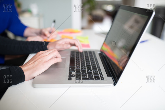 Close up of woman working on laptop while colleague takes notes on sticky notes in background