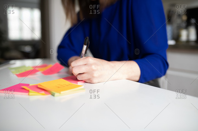 Close up of left handed woman writing on sticky note on table in kitchen