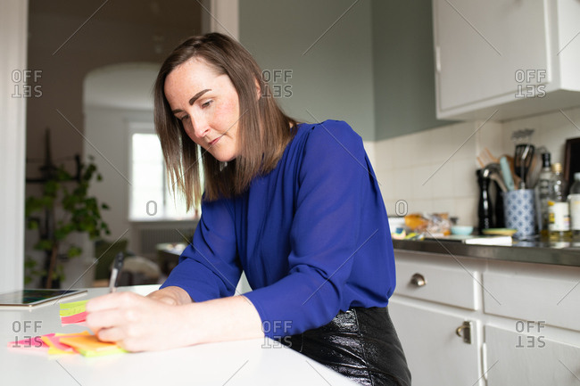 Woman writing on colorful sticky notes while working in kitchen at home