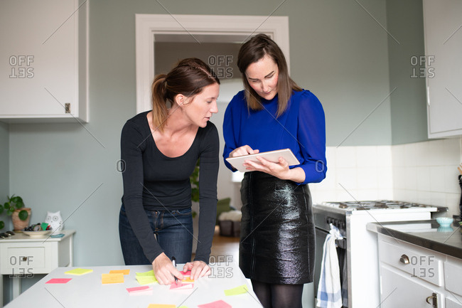 Woman checking tablet computer as colleague looks on while working from home in kitchen