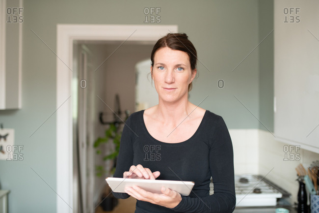 Portrait of woman using tablet computer looking to camera