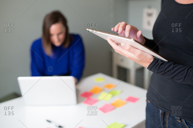 Woman standing working on tablet computer as co-worker sits at table working on laptop in background