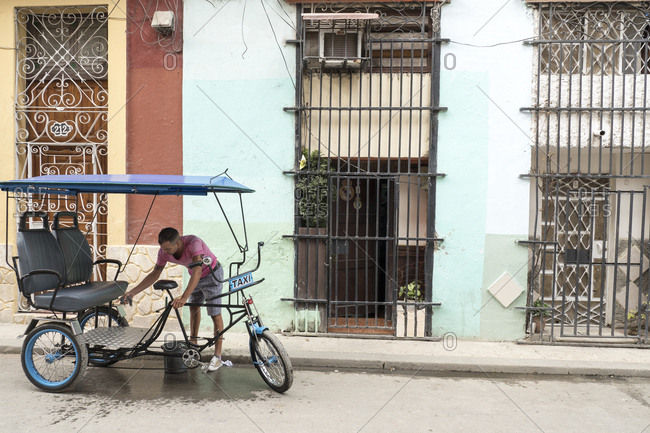 Havana, Cuba - February 19, 2015: A man washing bicycle rickshaw in front of apartment complex