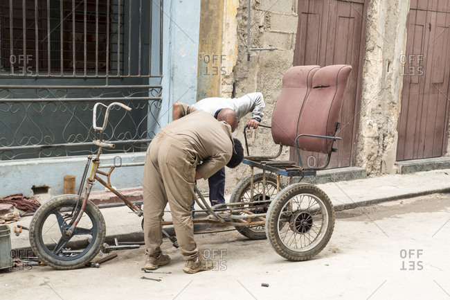 Havana, Cuba - February 19, 2015: A mechanic working to repair a bicycle rickshaw on the side of the street