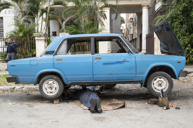 Havana, Cuba - February 21, 2015: A mechanic working under a car precariously propped up on homemade braces