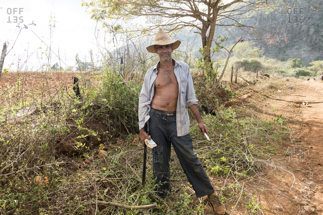 Vinales, Cuba - February 24, 2015: Portrait of farmer with shirt open standing in fields holding knife