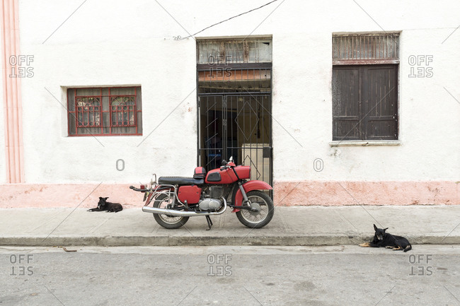 Cienfuegos, Cuba - February 26, 2015: Vintage motorcycle parked on sidewalk with only stray dogs for company