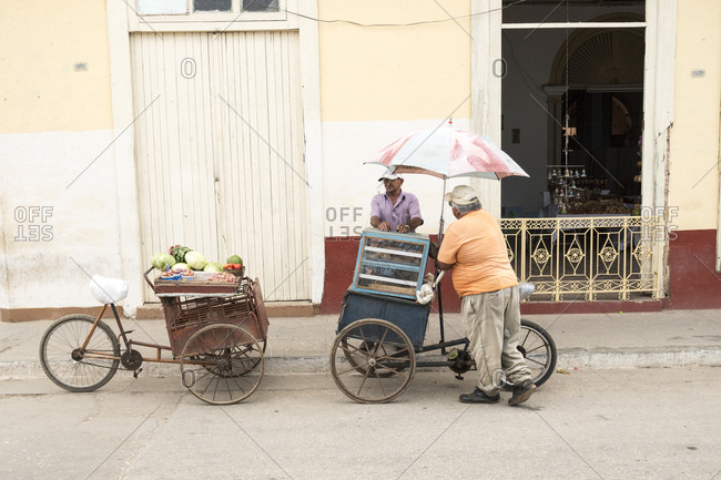 Cienfuegos, Cuba - February 26, 2015: Two street vendors pass the time talking next to their bicycle carts
