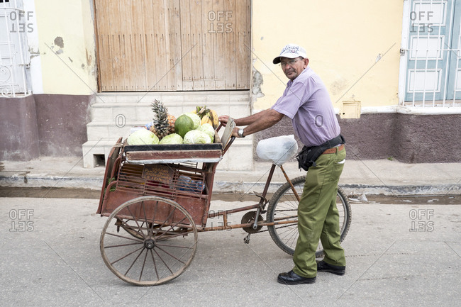 Trinidad, Cuba - February 27, 2015: Portrait of vegetable seller pushing his bicycle cart on the street
