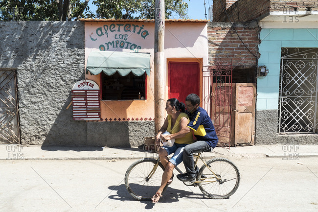 Trinidad, Cuba - February 27, 2015: Cuban man pedaling bicycle with wife as passenger past a small restaurant