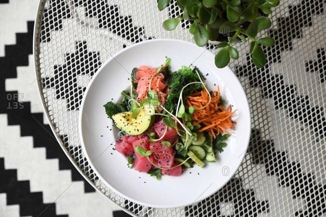 Poke bowl with tuna, carrots, cucumber, avocado and microgreens