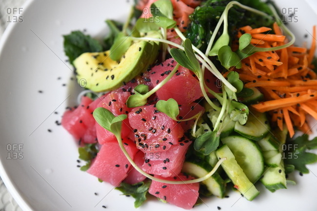Close up of a poke bowl with tuna, carrots, cucumber, avocado and microgreens