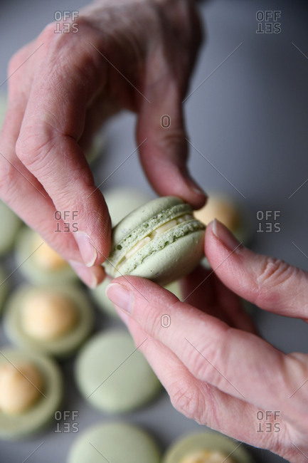 Hands pushing together macaron cookies