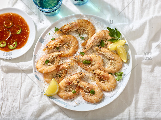 Overhead view of cooked shrimp on a bed of salt with salsa