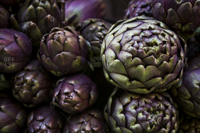 Piles of fresh artichoke bulbs for sale at a market stall in Bologna, Italy.