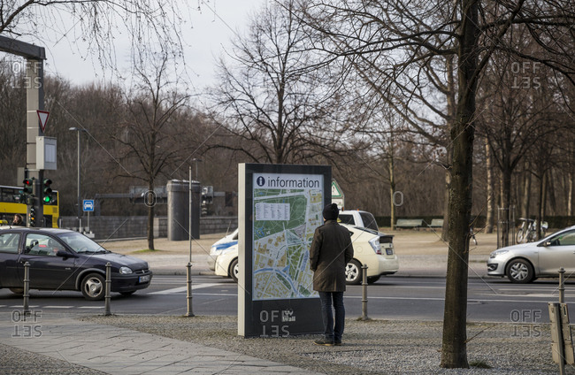 February 19, 2018: A man looks at a tourist information board in Berlin, Germany.