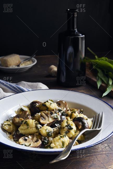 Gnocchi with fresh wild garlic and fried mushrooms on dark, rustic table
