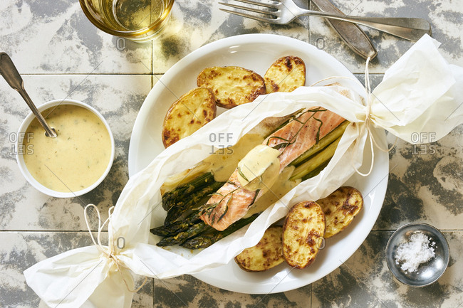 Green asparagus with salmon cooked in parchment paper, served with baked potatoes and tarragon sauce