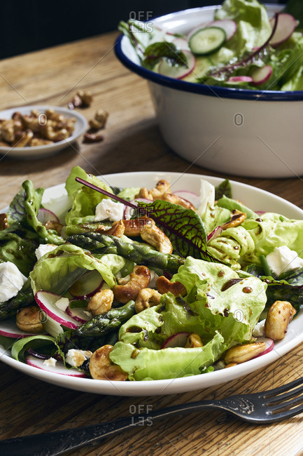 Mixed green salad with fried green asparagus on rustic table
