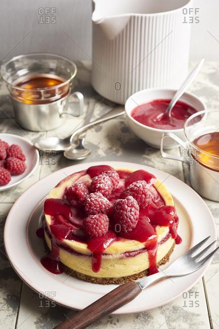 Homemade mini cheesecake with swirl of raspberry sauce topped with fresh raspberries